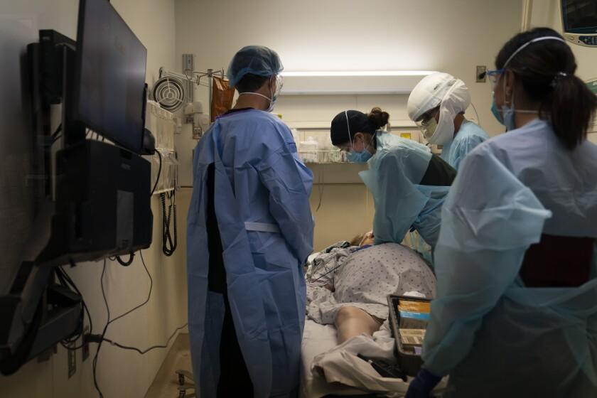 EMT Giselle Dorgalli performs chest compression on a COVID-19 patient Thursday.