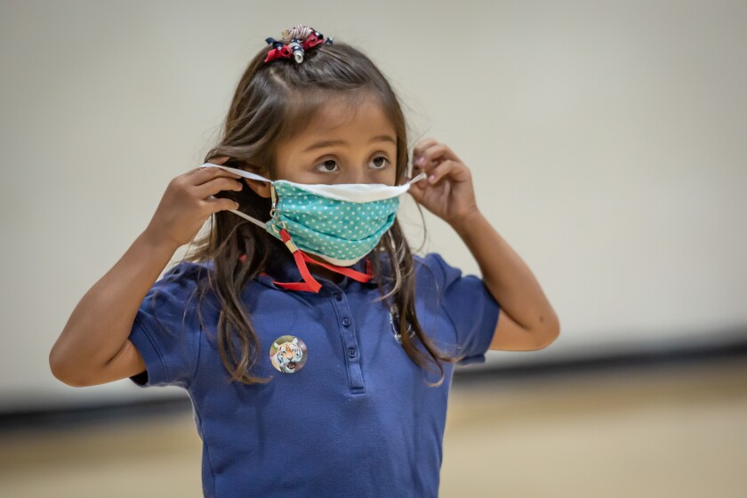 A little girl putting on a cloth face mask
