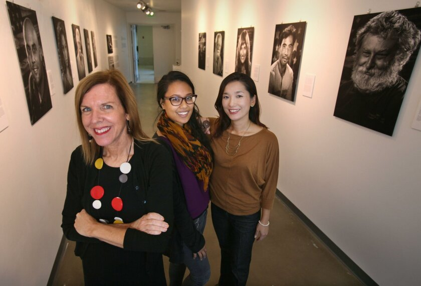 Candice Lopez, left, is curator of the VOICES exhibit honoring veterans at San Diego City College's Luxe Gallery. Student Desiree Robichaux, center, helped put together the exhibit and posters with adjunct graphic design professor Min Choi. The opening reception is Tuesday evening.