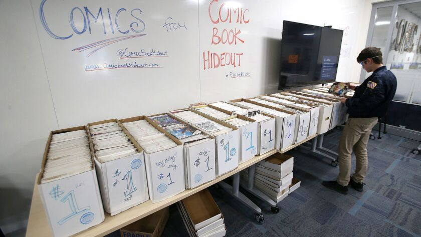 A student sifts through boxes of one dollar comic books at the first annual Fan Con at Laguna Beach