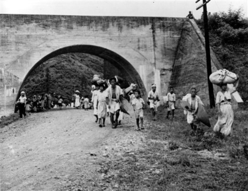 FILE - In this July 10, 1950 file photo, South Korean refugees are shown fleeing Taejon, South Korea, ahead of advancing North Korean troops early in the Korean War. In a political about-face, a South Korean commission investigating a century of human rights abuses, including the U.S. military's la