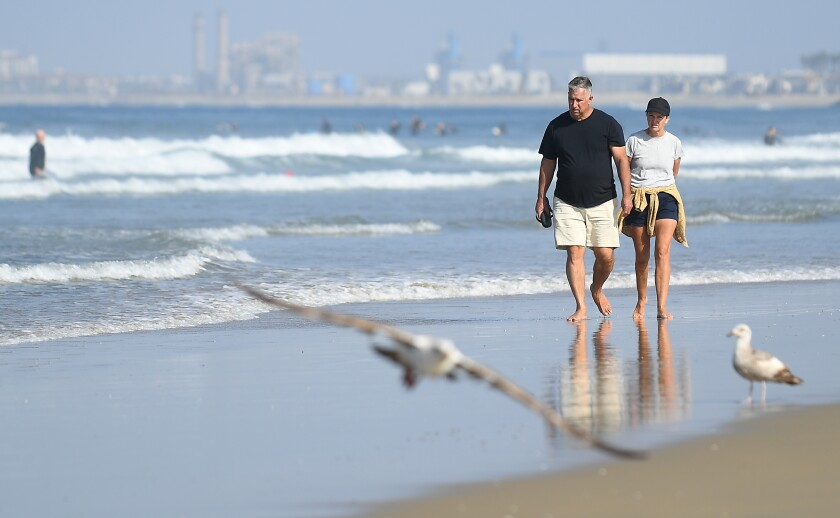 People walk along the shore in Newport Beach last weekend after Gov. Gavin Newsom closed all of Orange County's beaches to slow the spread of the coronavirus.