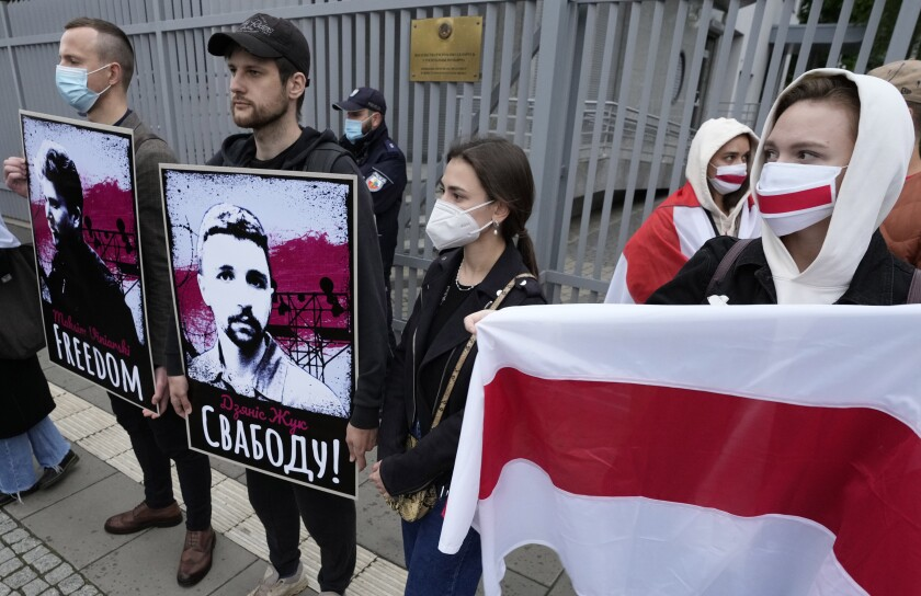 Protesters hold banners and flags during a demonstration demanding freedom for Belarus opposition activist Raman Protasevich, in front of the Belarus embassy in Warsaw, Poland, Tuesday, May 25, 2021. (AP Photo/Czarek Sokolowski)