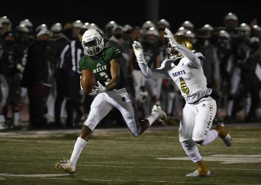 Helix High's Xavier Van fights for a pass with St. Augustine's DJ Overstreet during the first half of Friday night's game.