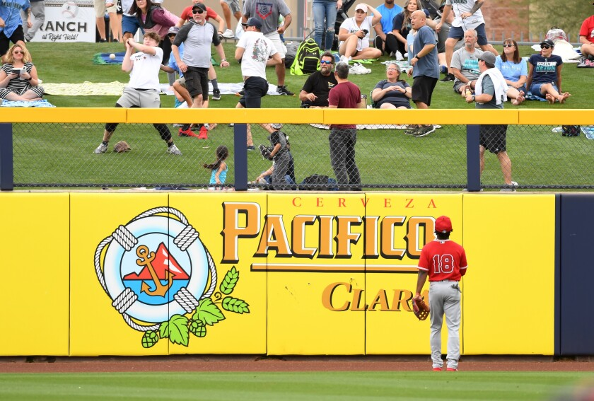 A young fan attempts to catch a home run ball hit by Seattle Mariners' Jose Marmolejos as Angels' Brian Goodwin looks on during the second inning of a spring training game at Peoria Stadium on Tuesday in Peoria, Ariz.
