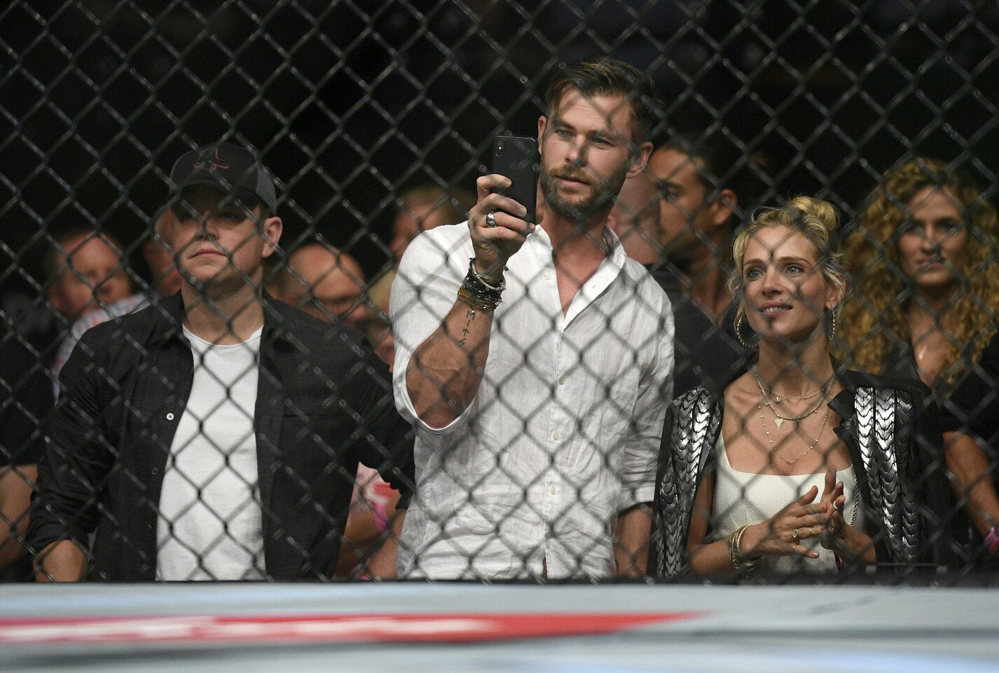 Actors, Matt Damon, left, Chris Hemsworth, center, and his wife Elsa Pataky watch Nigeria's Israel Adesanya and Brazil's Anderson Silva during their middleweight bout at the UFC 234 event in Melbourne, Australia, Sunday, Feb. 10, 2019. (AP Photo/Andy Brownbill)