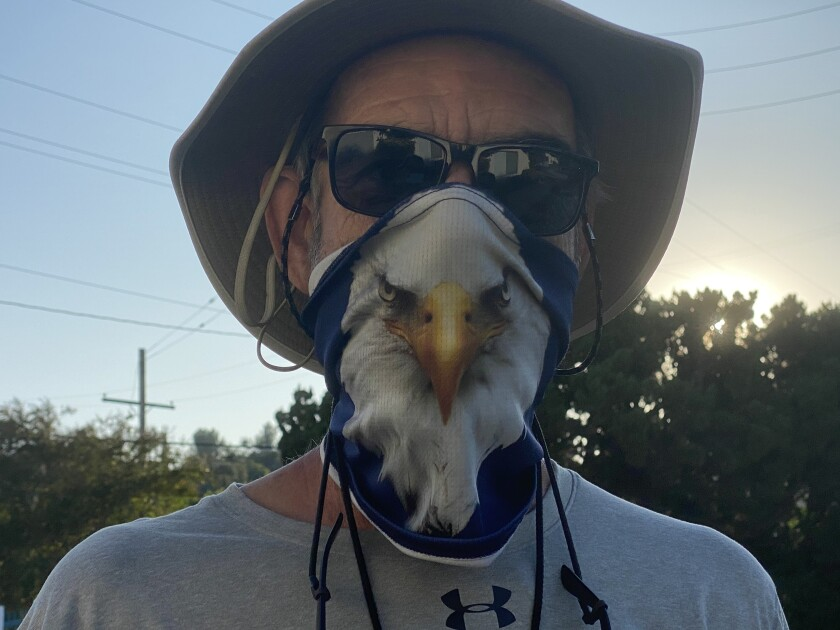 Chaminade football coach Ed Croson wears his Eagles face covering while directing his team through a conditioning program.