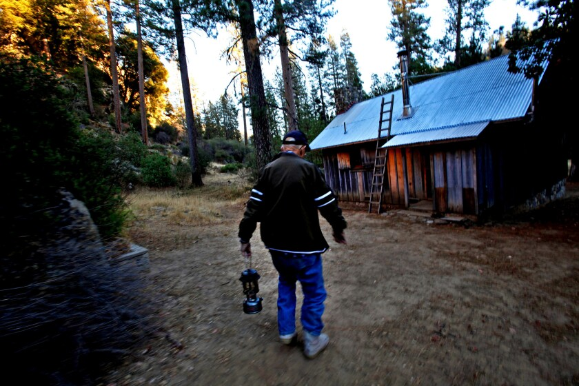 As night begins to fall and the lighting in the cabin grows dim, Jack English takes the Coleman lanterns outside to fill them with camp fuel.