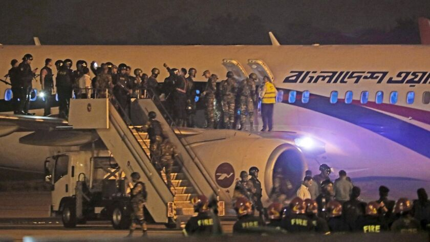 Bangladeshi security personnel stand guard at the airport in Chittagong on Sunday, following a Dubai-bound plane's emergency landing after a hijacking attempt.