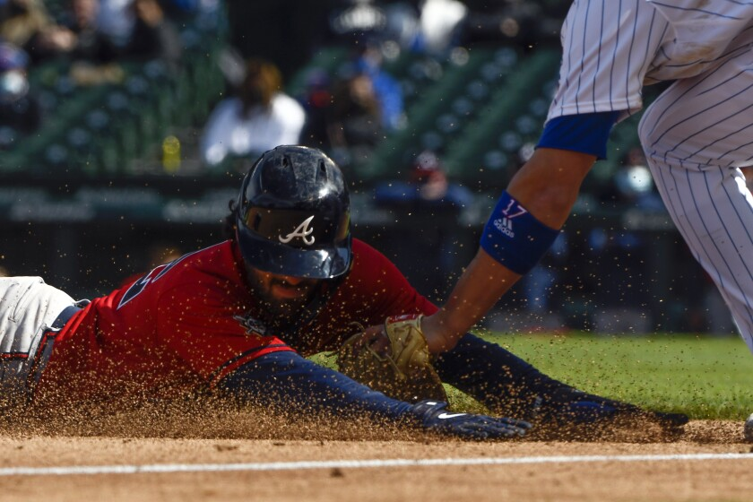 Atlanta Braves Dansby Swanson is tagged at third base by Chicago Cubs third baseman Kris Bryant during the fifth inning of a baseball game against the Friday, April 16, 2021, in Chicago. (AP Photo/Matt Marton)