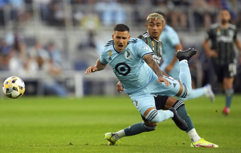 Minnesota United midfielder Franco Fragapane (7) goes flying as LA Galaxy defender Julian Araujo (2) stuck his foot out to defend during the first half of an MLS soccer match Saturday, Sept. 18, 2021, in St. Paul, Minn. (Anthony Souffle/Star Tribune via AP)