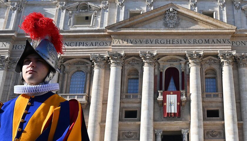 A Swiss guard stands in front of St Peter's Basilica before the appearance of Pope Francis