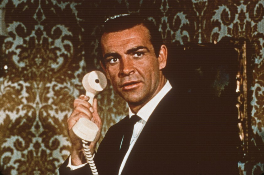 Sean Connery as James Bond holds a white telephone to his ear
