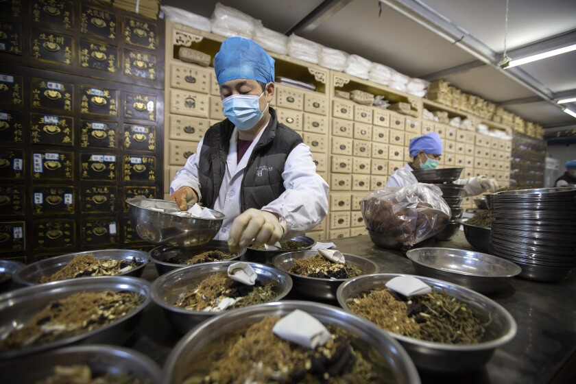 Workers fill prescriptions at a traditional Chinese medicine clinic in Beijing.