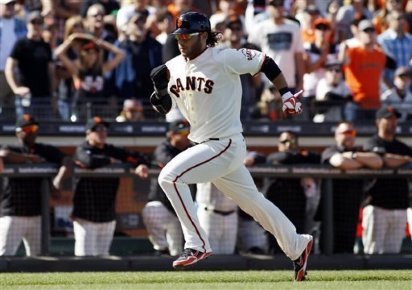 San Francisco Giants' Brandon Crawford scores on a Marco Scutaro sacrifice fly during the second inning of a baseball game against the Los Angeles Dodgers in San Francisco, Saturday, July 6, 2013. (AP Photo/George Nikitin)