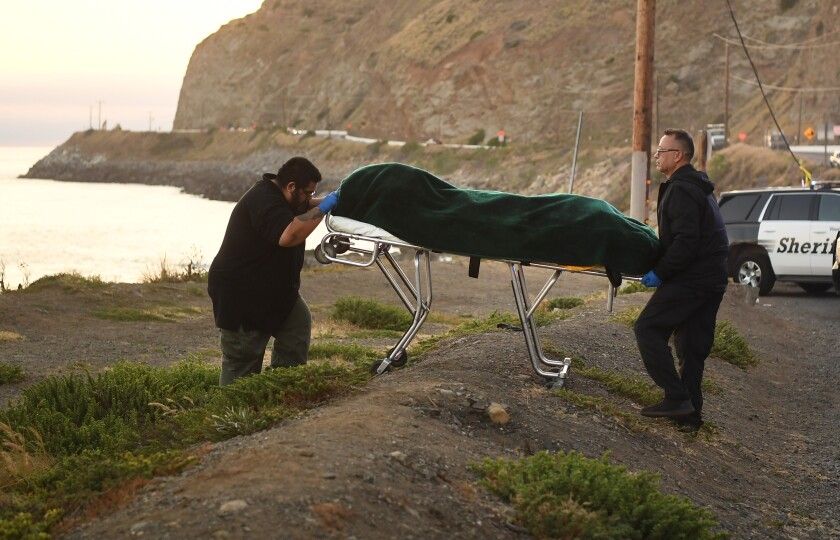 One of three drowning victims is carried away by Ventura County coroner's officials along Pacific Coast Highway