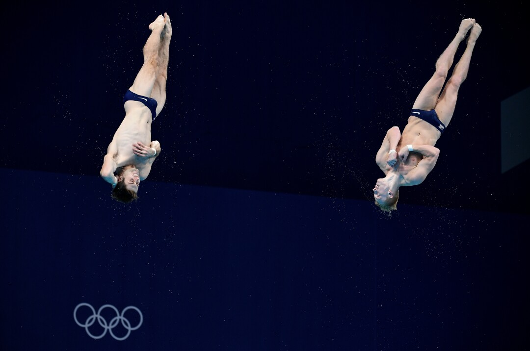 Two divers in midair.