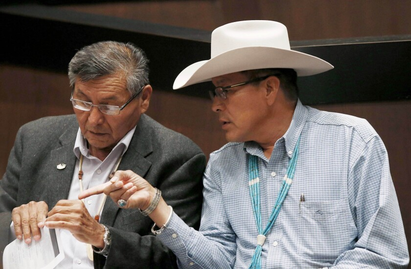 The Navajo Nation will receive $554 million from the U.S. to settle claims of mismanaged funds. Navajo Nation President Ben Shelly, left, talks with tribal presidential candidate Kenneth Maryboy this year.
