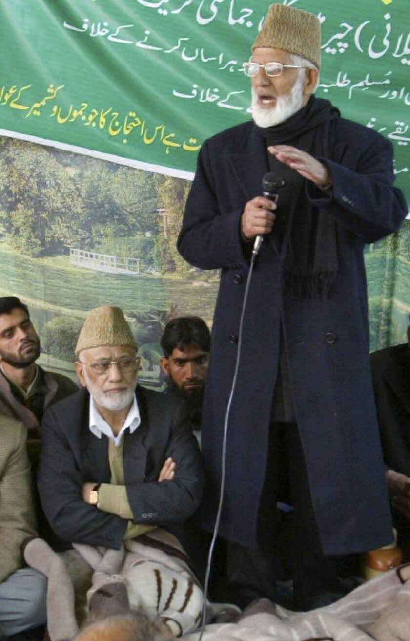 Mohammed Ashraf Sehrai, sitting wearing cap, listens as separatist leader Syed Ali Shah Geelani, standing, addresses a demonstration against the government in Srinagar, India, April 16, 2008. Sehrai, a prominent politician in Kashmir who challenged India's rule over the disputed region for decades died Wednesday while in police custody. He was 78. (AP Photo /Mukhtar Khan)