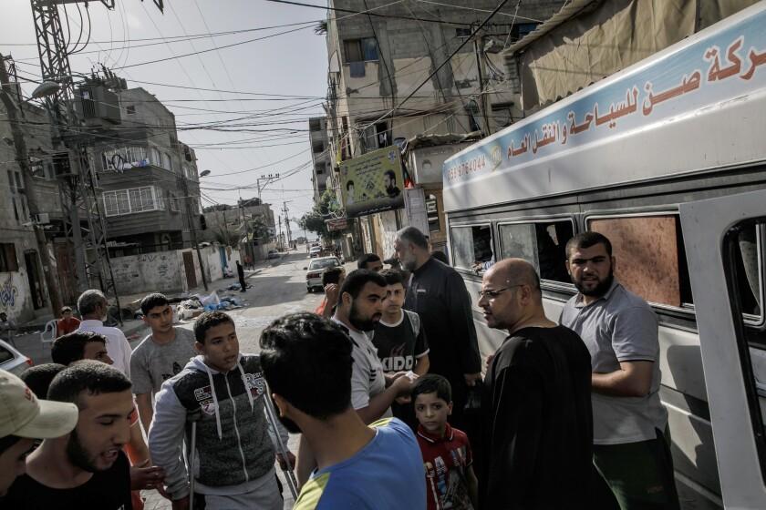 GAZA CITY, GAZA STRIP -- FRIDAY, MAY 18, 2018: Palestinians who live in Beach Camp, wait to board bu