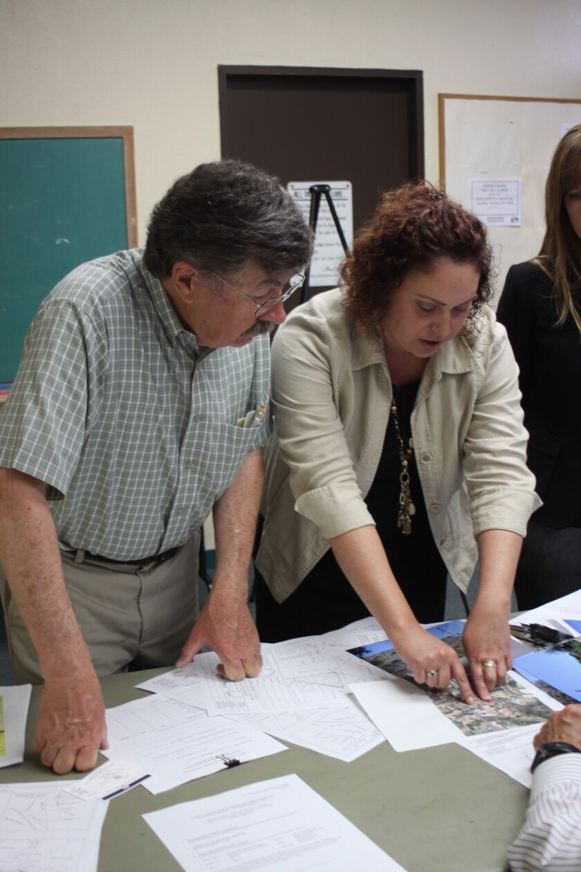 City of San Diego property agent Dena Boylan (right) shows maps and photos of the empty lot in question to DPR member Mike Costello.