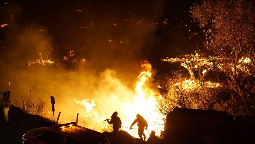 Firefighters battle the Lilac Fire in Bonsall in December 2017. The Moody's Investors Service this month downgraded all three investor-owned utilities in California over concerns about wildfire liability costs.
