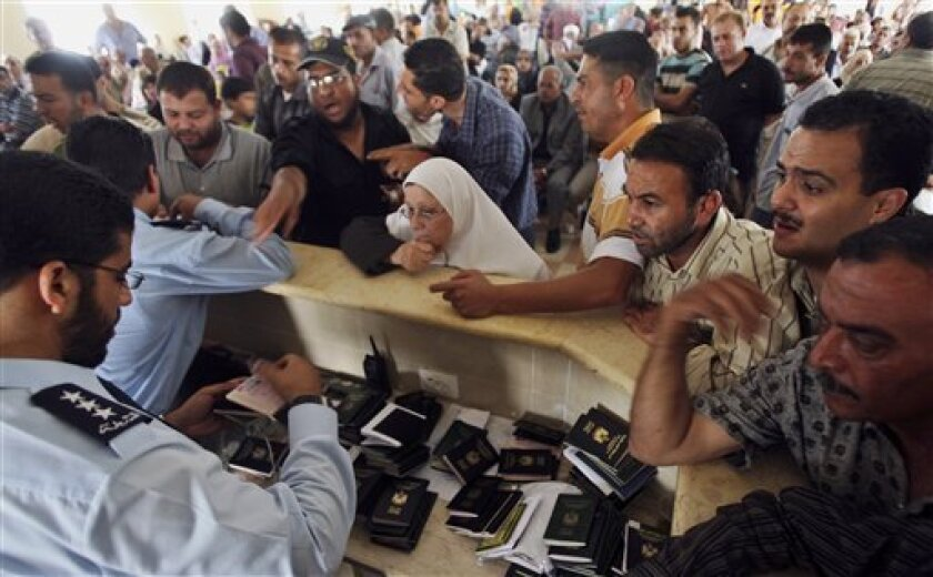 Palestinians wait for Hamas police officers to check their passports as they wait to cross to Egypt, at Rafah border crossing, southern Gaza Strip, Tuesday June 8, 2010. The opening of Gaza's gateway to the world has turned into a scene of extreme anxiety with hundreds crowding around border officials to learn when, and if, they can cross into Egypt. Gazans sealed in for three years are grateful just to have the hope after Israel's deadly raid on a blockade-busting flotilla focused attention on the Gaza Strip. (AP Photo/Eyad Baba)