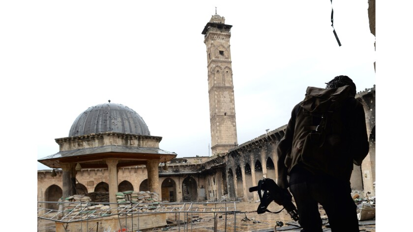 In a 2013 photograph, a rebel fighter faces the mosque's signature minaret, dating to 1090.