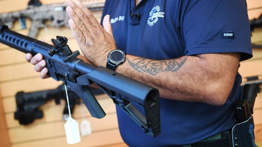 A salesman at a Virginia gun store demonstrates an AR-15 rifle fitted with a bump stock.
