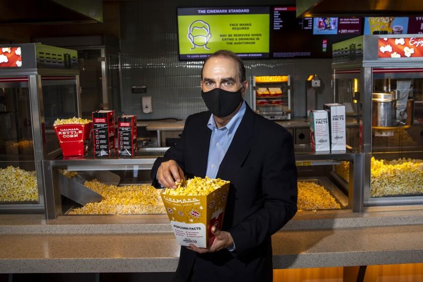 Cinemark CEO Mark Zoradi holding a bucket of popcorn
