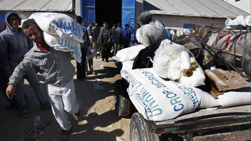A Palestinian man carries sacks of flour he received at a United Nations food distribution center in Shati refugee camp in Gaza City on Feb. 4, 2009.