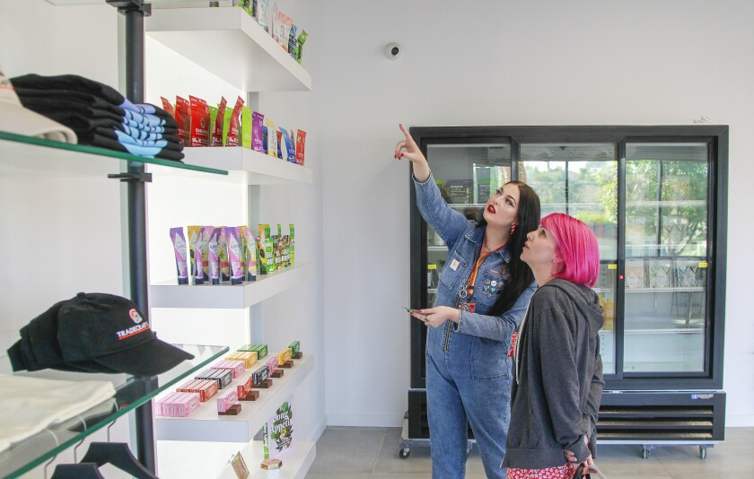Bud tender Shelby Fischer (left) explains some of the marijuana products to customer Krystle Paniagua at Tradecraft Farms.