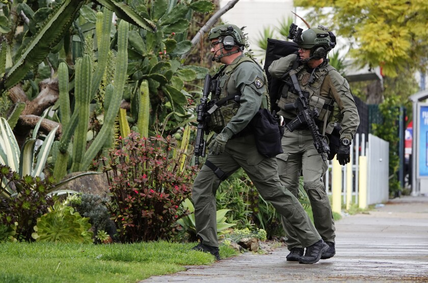 San Diego SWAT members walk along Fourth Ave. in Hillcrest as they respond to a possible suicidal man who fired a gun at police officers from a building.