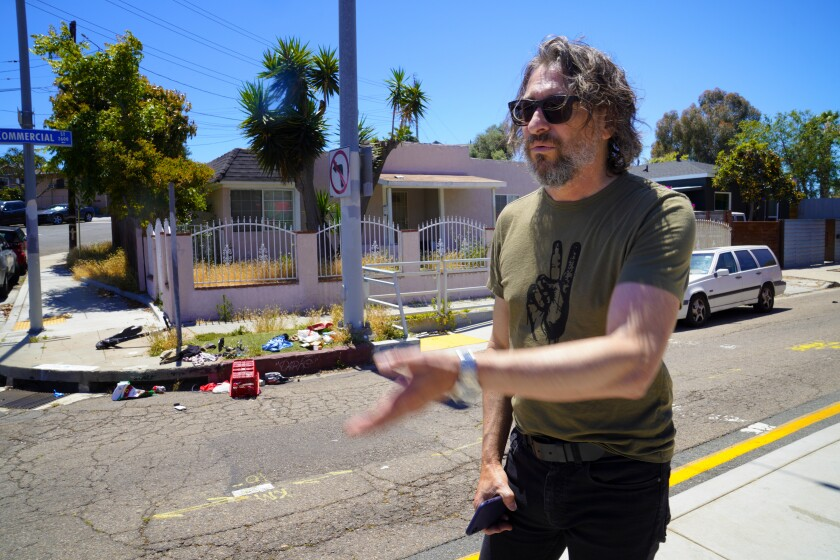 John Mireles, a Logan Heights property owner, gestures at trash on a corner of Commercial Street.