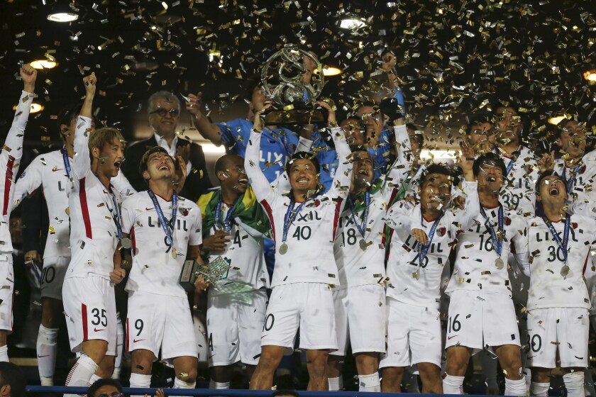 FILE - In this Nov. 10, 2018, file photo, Kashima Antlers' Mitsuo Ogasawara, center, holds up the trophy as he celebrates with teammates after winning the Asian Champions League at the end of their match with Iran's Persepolis the Azadi (freedom) stadium in Tehran, Iran. When the decision was made in 2013 to split the Asian Champions League into east and west geographic zones, it was unthinkable that a team from one half of the continent could book a place in the Grand Final weeks before some clubs on the other side hadn't started the group stage. Such a lopsided scenario will likely become a reality in 2020. (AP Photo/Vahid Salemi)