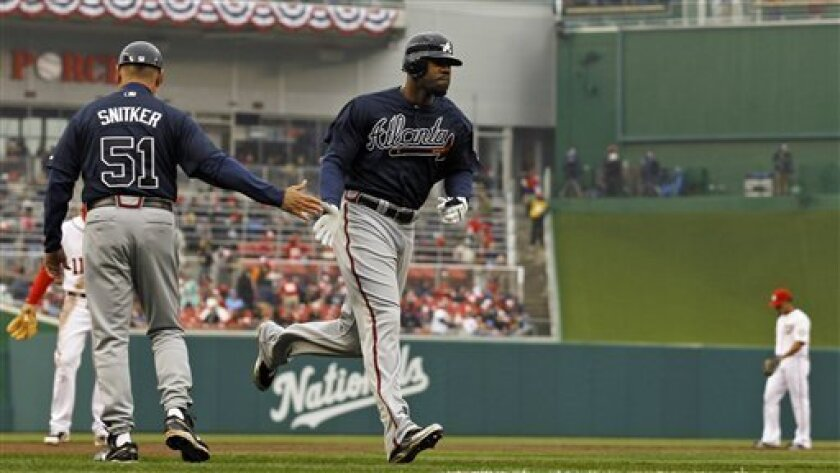 Atlanta Braves base runner Jason Heyward gets congrats from third base coach Brian Snitker after his solo home run in the second inning of their opening day baseball game with the Washington Nationals on Thursday, March 31, 2011 in Washington.(AP Photo/Alex Brandon)