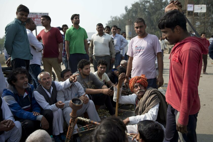 Protestors of India's Jat agricultural community block a highway linking New Delhi to Rohtak at Bahadurgarh, Haryana state, India, Saturday, Feb.20, 2016. Hundreds of army and paramilitary soldiers on Saturday tried to quell protests by angry mobs demanding government benefits in the northern Indian state, with at least four people killed in clashes between security forces and protesters, officials said. (AP Photo /Tsering Topgyal)
