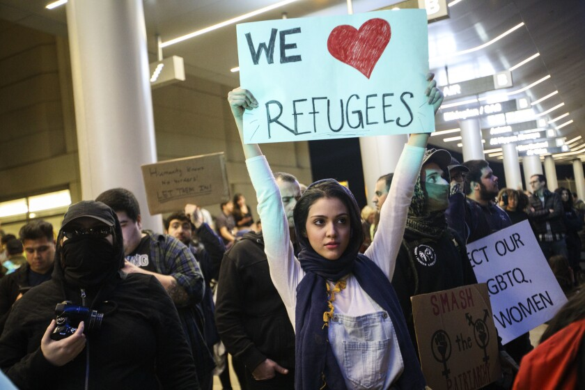 Protesters against President Trump's refugee plan gathered Sunday night at Los Angeles International Airport.
