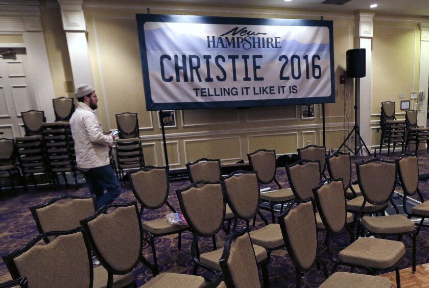 """Charlie Pearce, a campaign worker from Orange County, Calif., walks past a """"Christie 2016"""" sign while breaking down the primary night rally stage for Republican presidential candidate, New Jersey Gov. Chris Christie in Nashua, N.H., Wednesday, Feb. 10, 2016. (AP Photo/Charles Krupa)"""
