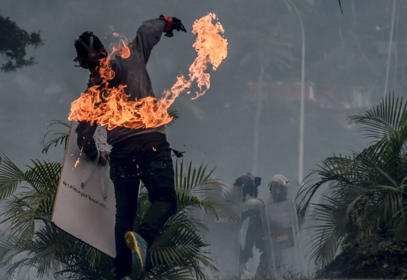 An opposition activist clashes with riot police during a demonstration against the government of Venezuelan President Nicolas Maduro in Caracas on Monday.