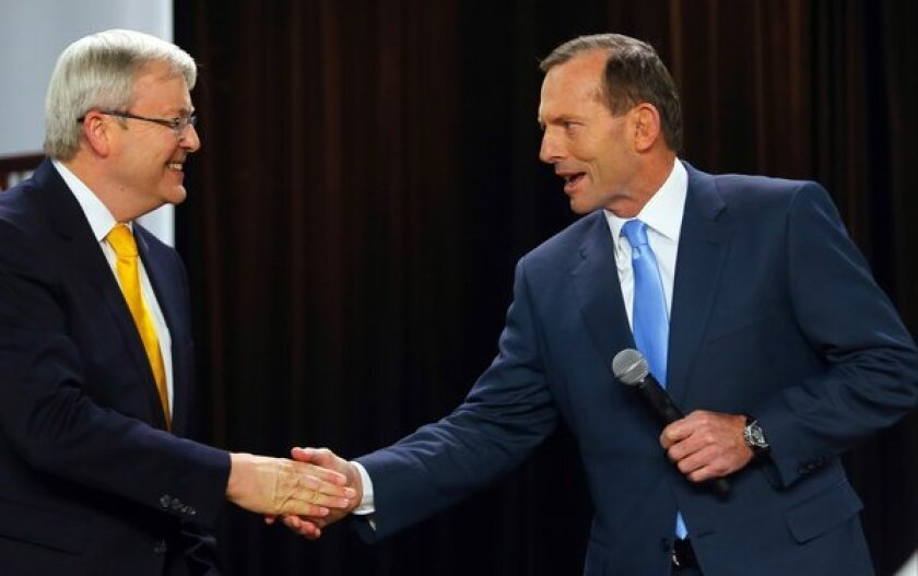 Australian opposition leader Tony Abbott, right, greets incumbent Prime Minister Kevin Rudd at the start of a people's forum in Brisbane last month. Abbott's Liberal-National conservative coalition is tipped to win a clear majority of seats in Saturday's parliamentary voting, propelling the party leader into the prime minister's office.