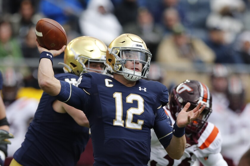 Notre Dame quarterback Ian Book (12) throws during the first half against Virginia Tech on Saturday.