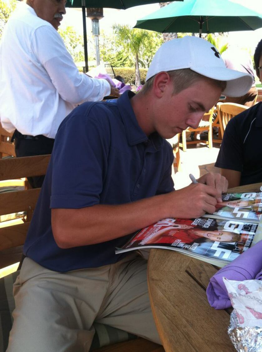 Jake Knapp signs Southland Golf magazine covers that feature his picture after his round on Wednesday.