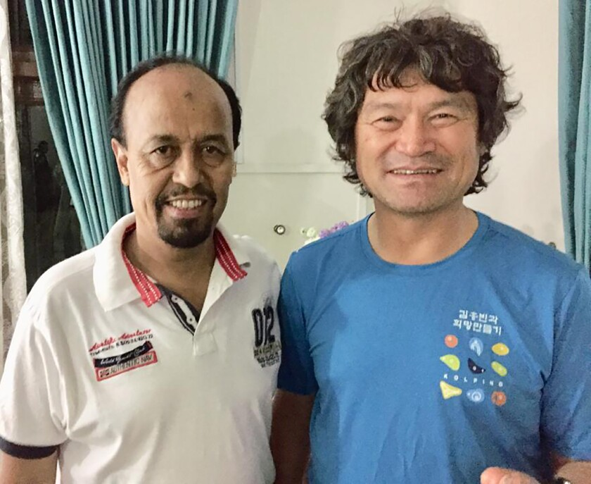 In this undated photo released by the Pakistan Alpine Club on Tuesday, July 20, 2021, shows club's secretary Karrar Haidri, left, and the now missing Korean climber Kim Hong Bin posing for a photograph, in Islamabad, Pakistan. The famous fingerless South Korean climber Kim Hong Bin fell into a crevasse and went missing after scaling the world's 14th one of the highest peaks in northern Pakistan and a search mission is being planned to trace him, a Pakistani mountaineering official said Tuesday. (Pakistan Alpine Club via AP)