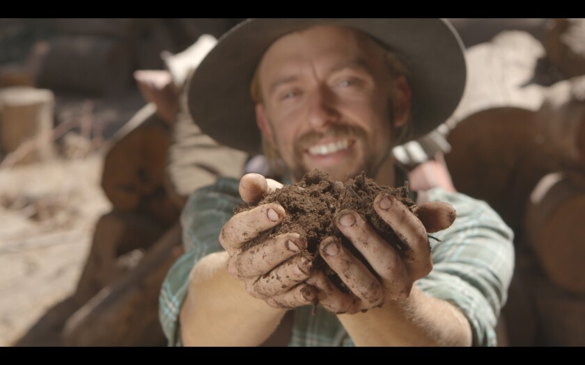 "A farmer holds a handful of dirt in the documentary ""Kiss the Ground."""
