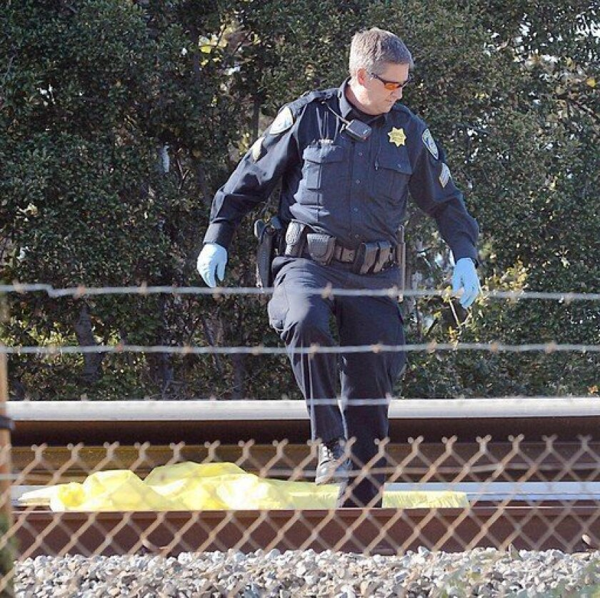 A BART police officer looks along the track where two maintenance workers were struck and killed by a train Saturday, the second day of a strike by transit workers.