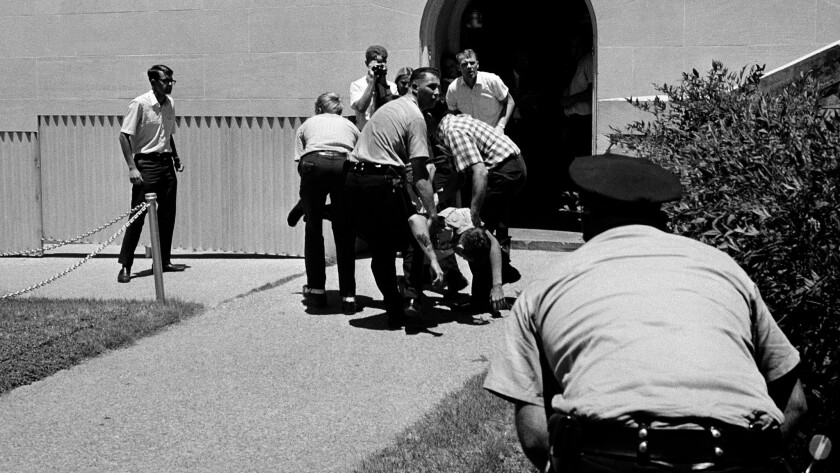 An Austin policeman is carried to a waiting ambulance after being critically wounded by a sniper on the 24th floor of the University of Texas tower, Aug. 1, 1966 in Austin as another police officer crouches behind bushes.