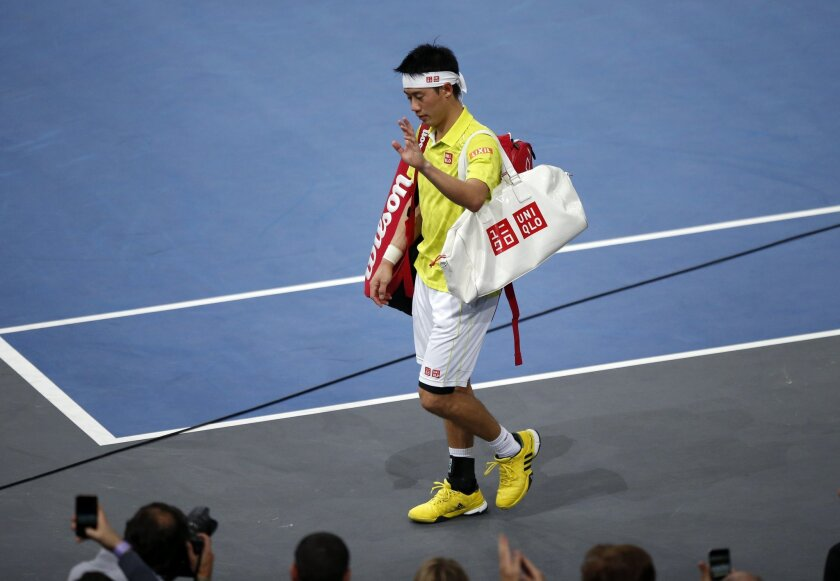 Japan's Kei Nishikori leaves the court after retiring against France's Richard Gasquet during their round of sixteen match of the BNP Masters tennis tournament, at the Paris refurbished Bercy Arena, in Paris, France, Thursday, Nov. 5, 2015. (AP Photo/Francois Mori)