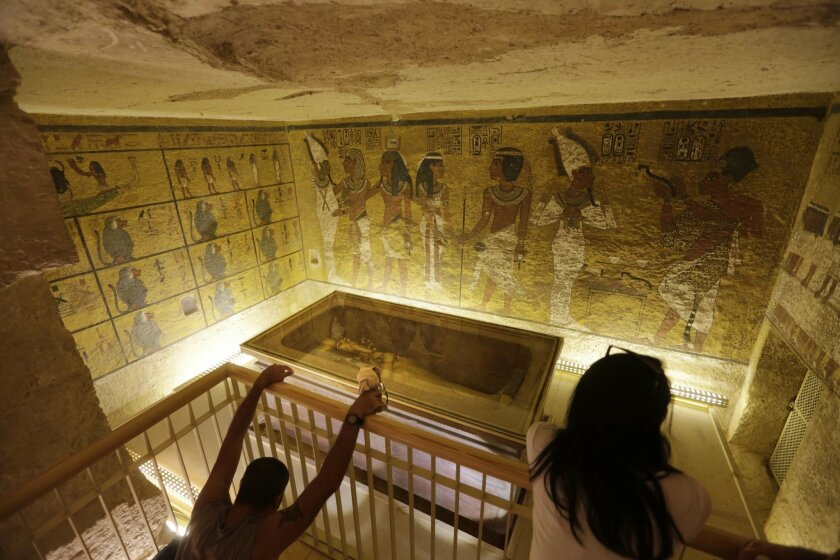 Tourists look at the tomb of King Tut as it is displayed in a glass case at the Valley of the Kings in Luxor, Egypt, Thursday, Nov. 5, 2015. (AP Photo/Amr Nabil)