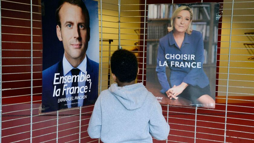 A boy looks at the two French presidential candidates as French citizens cast their vote at the Fren